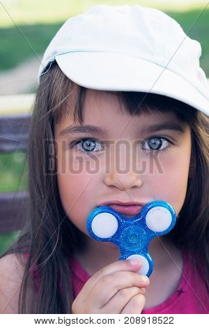 Little caucasian girl with Fidget Spinner held up to his chin outdoors. Crazy toy of 2017.