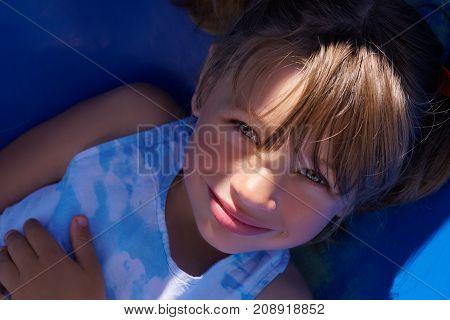 Smiling girl having fun on children's slide. A ray of sunlight passes over her face.