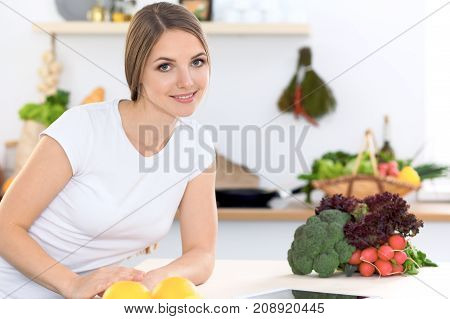 Young woman at the kitchen making online shopping by tablet computer and credit card.