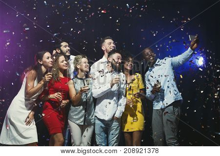 Party people. Group of young joyful friends having fun at birthday party at night club, showered with confetti, drinking champagne, taking selfie on smartphone. Enjoying life and celebration concept