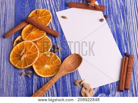 Christmas decoration. Blank for recipes with dried orange slices, cinnamon and spices on a wooden background.