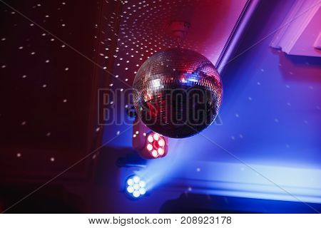Disco ball with searchlight bright rays. Background night party