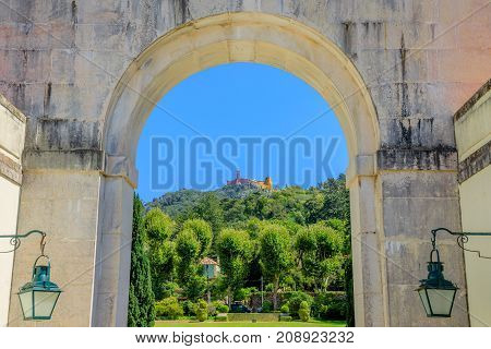 Popular landmark of Pena National Palace in the beautiful blue sky above Sintra, seen from arch of Seteais Palace, a neoclassical palace. Sintra historic center, Lisbon District in Portugal.