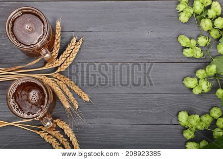 glass of foamy beer with hop cones and spikelets of wheat on black wooden background. Top view with copy space for your text.