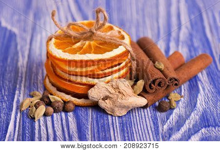 Dry slices of orange, cinnamon, pimento and cardamom, on a blue wooden background. Aromatic spices.