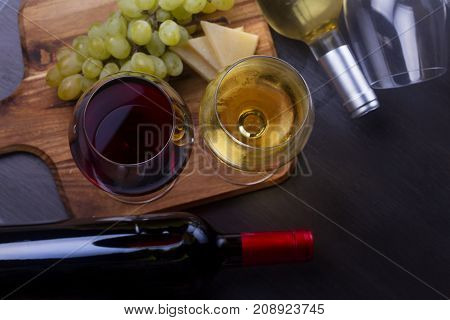 Red and wite wine in glasses with grape fruit, top view