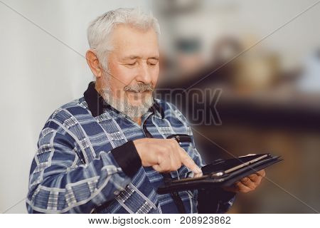 Old man sitting on home and reading new on his tablet computer