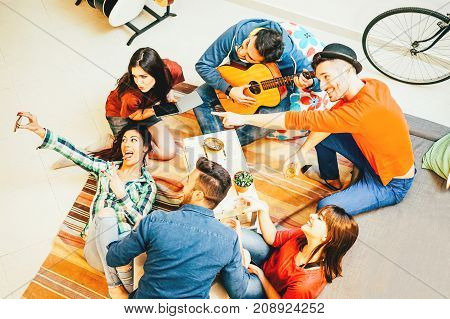 Group of funny friends enjoying together playing music with guitar and taking selfie with mobile phone - Happy young people having fun in the living room at home - Concept of friendship