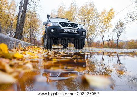 KHABAROVSK RUSSIA - OCTOBER 14 2017: Mitsubishi Pajero Sport in autumn street near a puddle