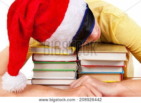 Student in Santa Hat sleep on the Books on a Table
