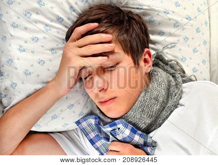 Sad and Sick Young Man in the Bed at the Home