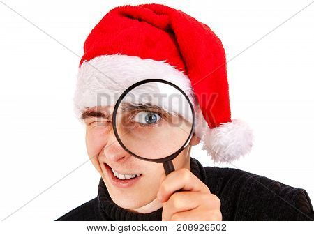 Young Man in Santa Hat with Magnifying Glass on the White Background