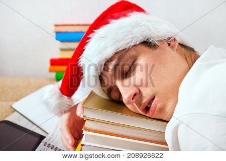 Tired Young Man in Santa's Hat sleep on the Books