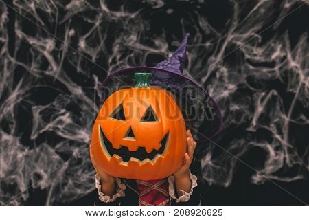 Little girl dressed as a witch holding a pumpkin against a dark background with spiderwebs