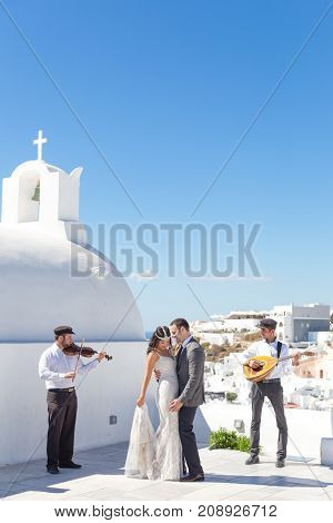 Oia, Santorini island, Greece - Oct 11, 2017: Bride and groom dancing during wedding ceremony with traditional musicians and singers on Santorini island on 11th of October, 2017 on Santorini, Greece.