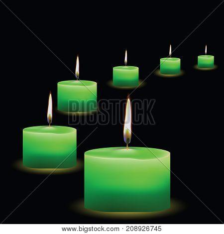 Set of burning green candles isolated on black background