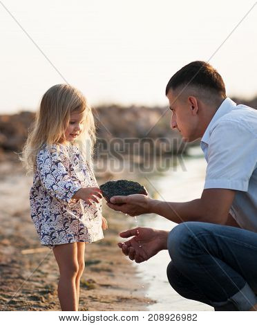 Young father shows his small daughter a stone near the river