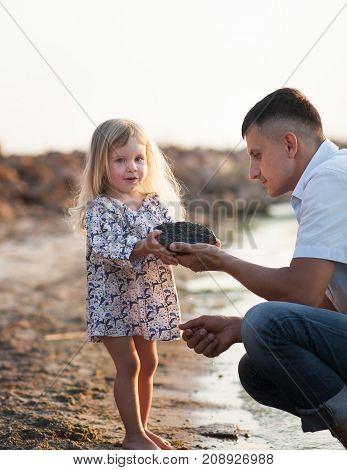 Young father spends his time with his little daughter on the river's coast.