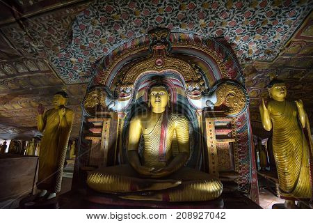 Meditating Buddha under makara torana in Maha Aluth Viharaya at buddhists cave temple in Dambulla, Sri Lanka. Images of Mahayana Bodhisattvas : Maitreya on left and Natha or Avolokatesvara on right