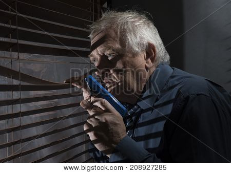 Mature man holding a gun looking out of a window with blinds casting shadows