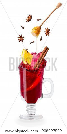 mulled wine with flying ingredients: slice of orange, cinnamon stick, anise stars, cloves and honey isolated on white background. Splash. Christmas drink. Alcohol cocktail