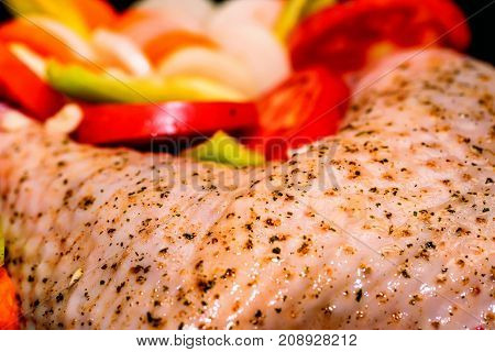 Close-up of raw turkey garnished with potato, vegetables and cranberries in a rustic style before preparing in oven