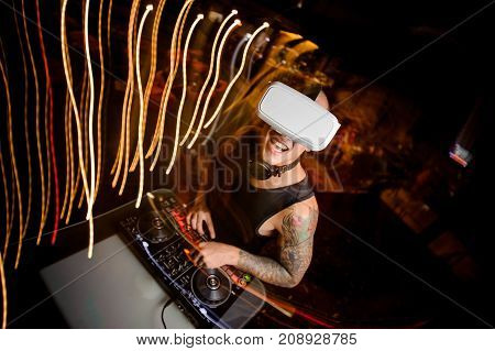 Smiling DJ in virtual reality glasses dressed in black shirt and with tattoo mixes music in club