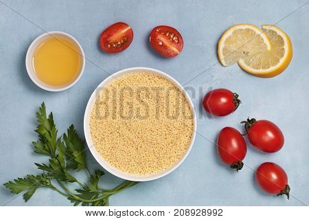couscous and fresh vegetables: tomatoes peppers lemon parsley olive oil on a blue background. view from above