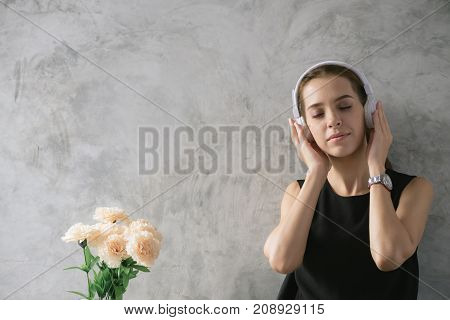 Woman love music. Young woman listening music while thinking woman doing homework in modern place woman working with happy emotion concept. Portrait of happy woman listening musical. Pretty woman listening music with her headphones in the home.