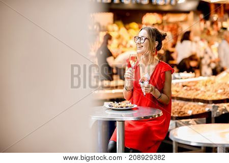 Young woman in red dress eating jamon traditional spanish dry-cured ham sitting at the Barcelona food market