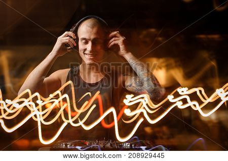 Smiling tattooed DJ in headphones on the background of night club lights with closed eyes