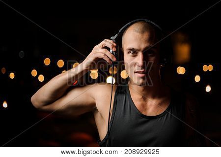 Young nightclub DJ in headphones feels the music on the background of night club lights