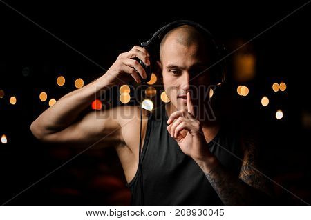 Young and tattooed nightclub DJ in headphones feels the music on the background of night club lights