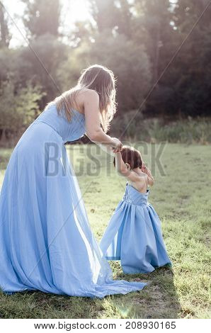 Mom with daughter in blue long indentical dresses on grass in forest