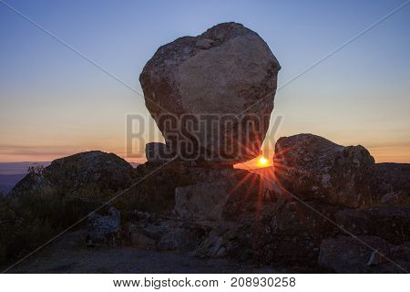 Sun rising between megalithic monument of Cancho Que Se Menea. In English shifting rock. Montanchez Spain