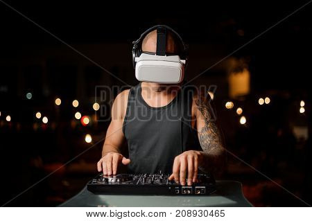 Muscular nightclub DJ in night vision glasses with headphones plays the music on the background of lights