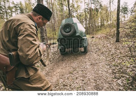 Pribor, Belarus - April 23, 2016: Re-enactor Dressed As Soviet Russian Red Army Infantry Soldier Of World War II Running In Attack With Rifle Under Cover Of An Armored Car In Forest At Spring Season