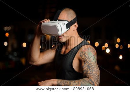 Muscular and tattooed handsome man dressed in black shirt in night vision glasses on the background of lights
