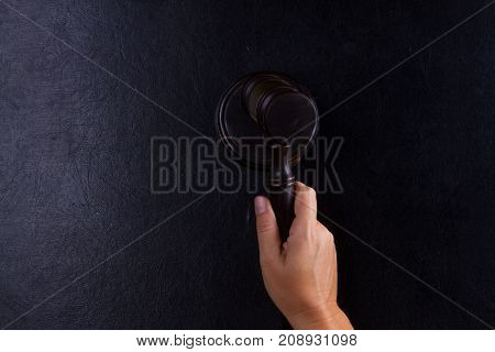 Hand holding law gavel - law and justice concept, copy space on black leather background