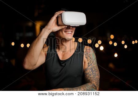 Muscular and tattooed smiling handsome man dressed in black shirt in night vision glasses on the background of lights