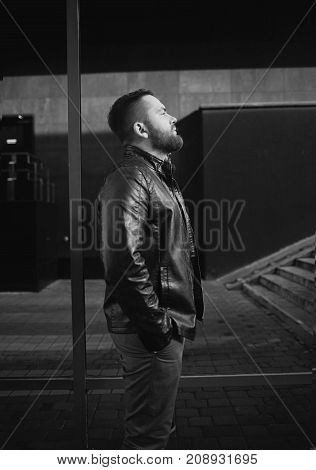 Black and white image of attractive pensive young man looks into the distance