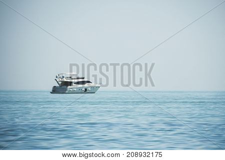 White yacht in the blue sea against a clear blue sky background.