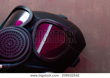 Black gas mask with pink reflection in the glass on a beautiful background.