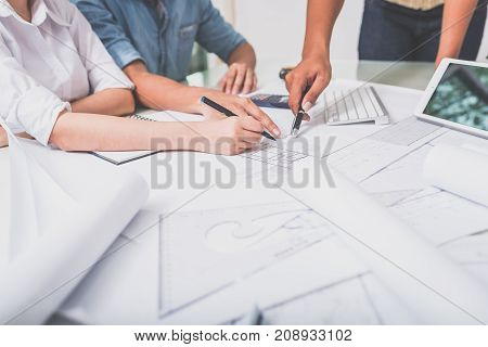 Close up hand of business people pointing at blueprint and document during team meeting on working table