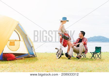 Happy Asian couple having a good time together while travel camping vacation trip by the lake