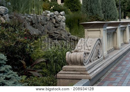 Stone bridge from balustrades in Greek style in park