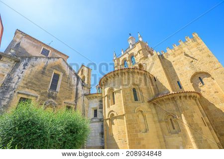 Behind the Old Coimbra Cathedral in a sunny day. Se Velha de Coimbra, is one of most important romanesque buildings in Portugal and landmark in university center town of Coimbra, north of Portugal.