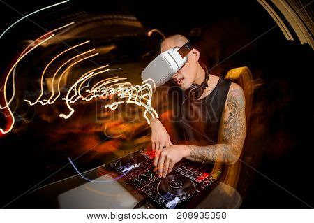 Man in glasses of virtual reality enthusiastically plays on a DJ mixer against the background of a night city