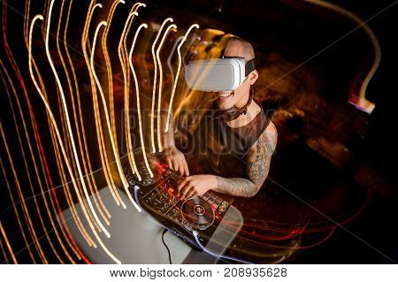 Smiling DJ man in virtual reality glasses on the background of a party. The concept of future technologies.