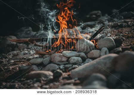 the smoldering fire on the river bank